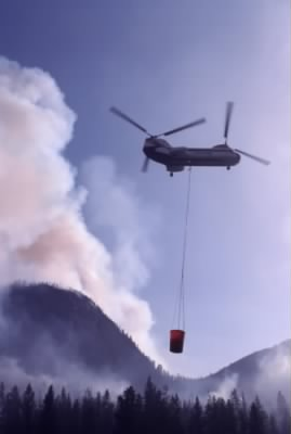 Helicopter using a river water to douse fire