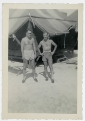 William E. Prettyman and friend in shorts outside a tent on the Kwajalein Atoll